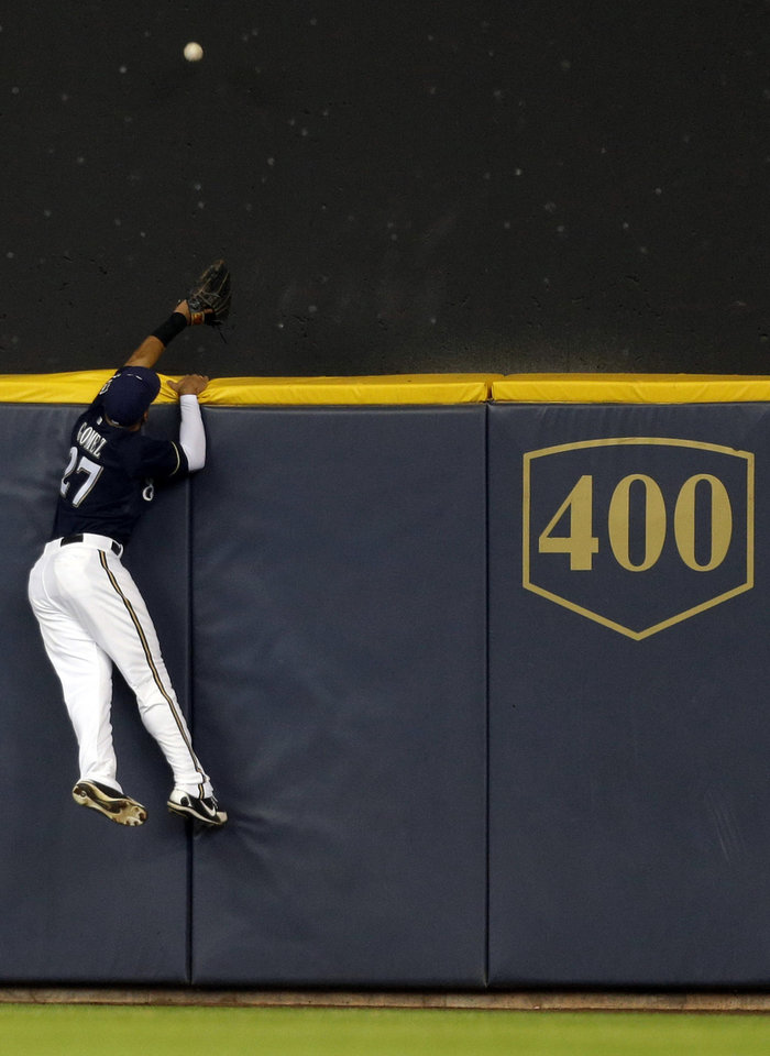 Photo - Milwaukee Brewers' Carlos Gomez cannot reach a home run hit by Chicago Cubs' Starlin Castro during the second inning of a baseball game on Sunday, April 27, 2014, in Milwaukee. (AP Photo/Jeffrey Phelps)