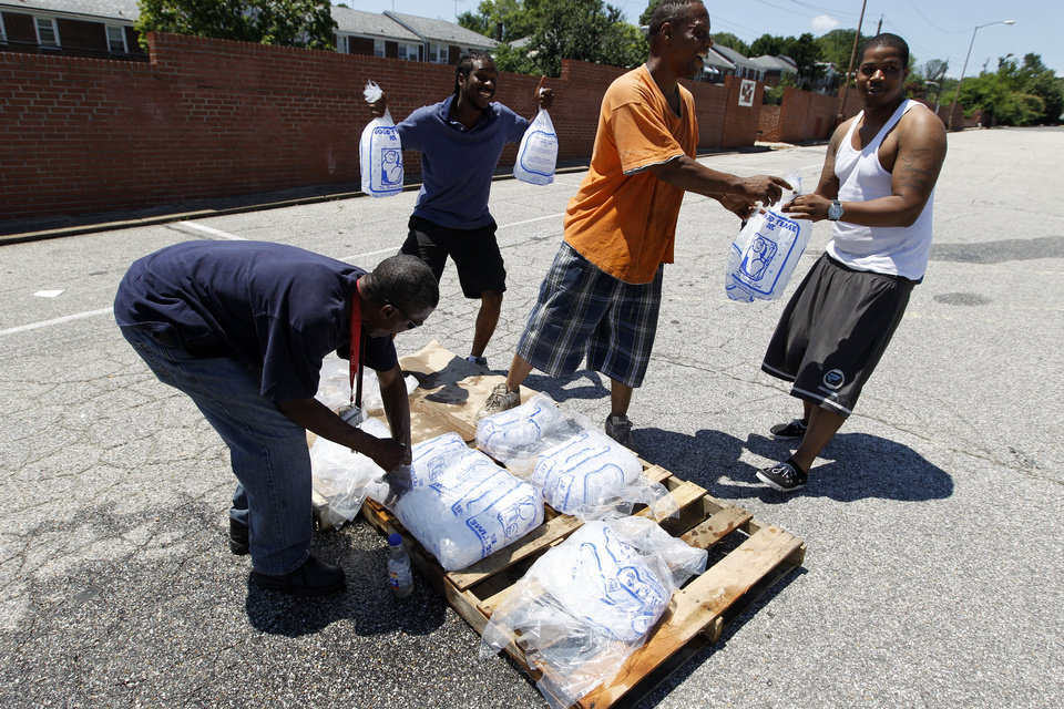 Photo -   City workers George Kirk, right, and Joe Lane give away free bags of ice to residents at the Northwood Plaza shopping center in Baltimore on Monday July 2, 2012. Around 2 million customers from North Carolina to New Jersey and as far west as Illinois were without power Monday morning after a round of summer storms. (AP Photo/Jose Luis Magana)