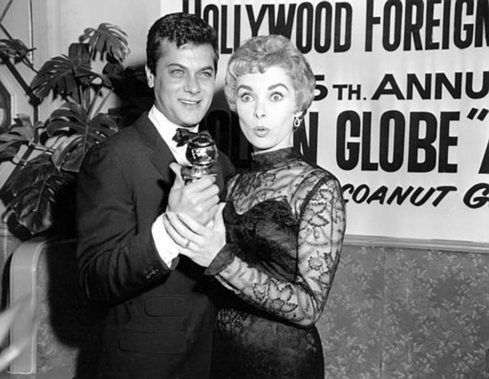 """Tony Curtis holds his Golden Globe award for World Male Film Favorite as his wife, actress Janet Leigh, gives a look of surprise at the Hollywood Foreign Press Association awards dinner at the Coconut Grove in Hollywood, Calif., Feb. 26, 1958. Curtis was nominated, but did not win, in the best actor category for """"The Defiant Ones,"""" which won best picture. (AP Photo)"""