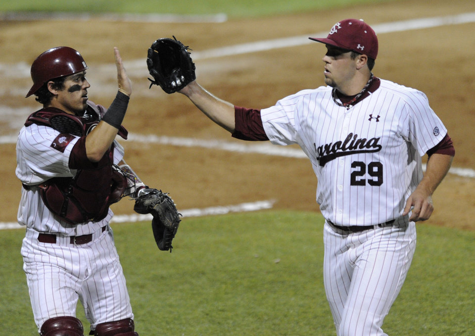 Photo - South Carolina pitcher Michael Roth, right, celebrates with catcher Dante Rosenberg, left, while throwing against Oklahoma in the fourth inning of an NCAA college super regional baseball tournament game in Columbia, S.C., Saturday, June 9, 2012. (AP Photo/Mary Ann Chastain) ORG XMIT: SCMC105
