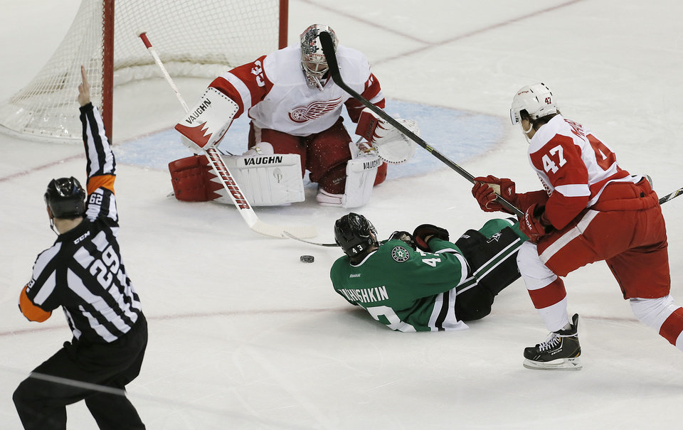 Photo - Detroit Red Wings defenseman Alexei Marchenko (47) is called for hooking as Dallas Stars forward Valeri Nichushkin (43) attempts a shot on goalie Jimmy Howard (35) in the first period of an NHL hockey game, Saturday, Jan. 4, 2014, in Dallas. (AP Photo/Brandon Wade)