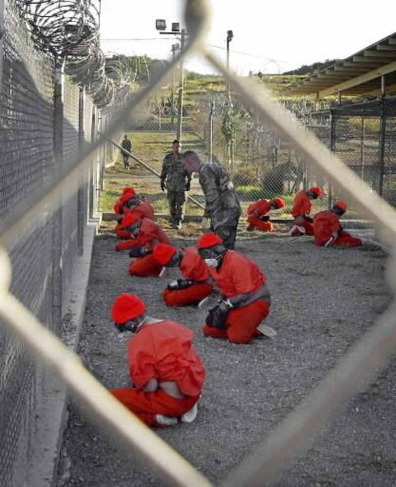 In this Jan. 11, 2002 file photo, released by the Department of Defense, detainees wearing orange jump suits sit in a holding area as military police patrol during in-processing at the temporary detention facility Camp X-Ray on Guantanamo Bay U.S. Naval Base in Cuba. (AP Photo/U.S. Navy, Shane T.McCoy, File)