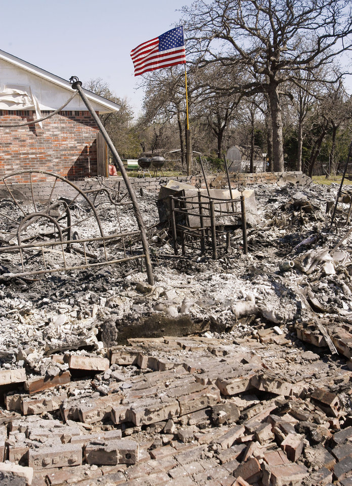 Photo - Homeowners have placed an American flag over the remains of their home which burned just south of Choctaw High School in Choctaw, Okla.,  Saturday, April 11, 2009. Photo by Paul Hellstern, The Oklahoman