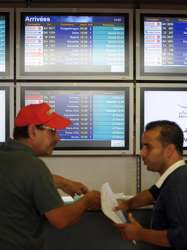 Photo - People stand next to an arrival information screen showing the delayed Air Algerie flight 5017 at the Houari Boumediene airport near Algiers, Algeria, Thursday, July 24, 2014. An Air Algerie flight carrying 116 people from Burkina Faso to Algeria's capital disappeared from radar early Thursday over northern Mali and