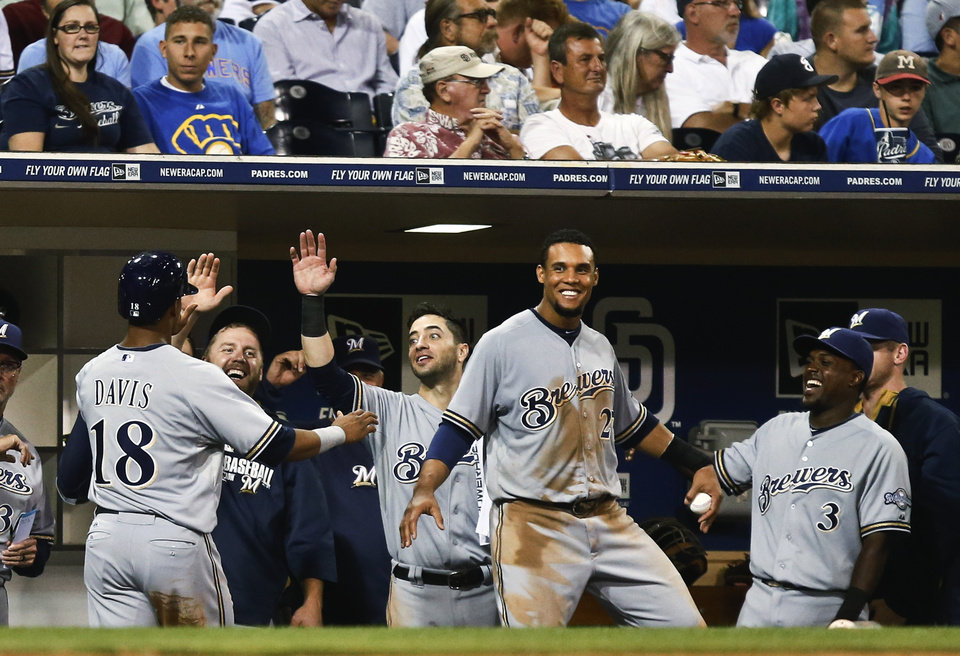 Photo - Milwaukee Brewers' Khris Davis is congratulated by Ryan Braun after scoring as Carlos Gomez does a dance for teammate Martin Maldonado after Maldonado singled home Davis in the third inning of a baseball game against the San Diego Padres on Monday, Aug. 25, 2014, in San Diego.  (AP Photo/Lenny Ignelzi)