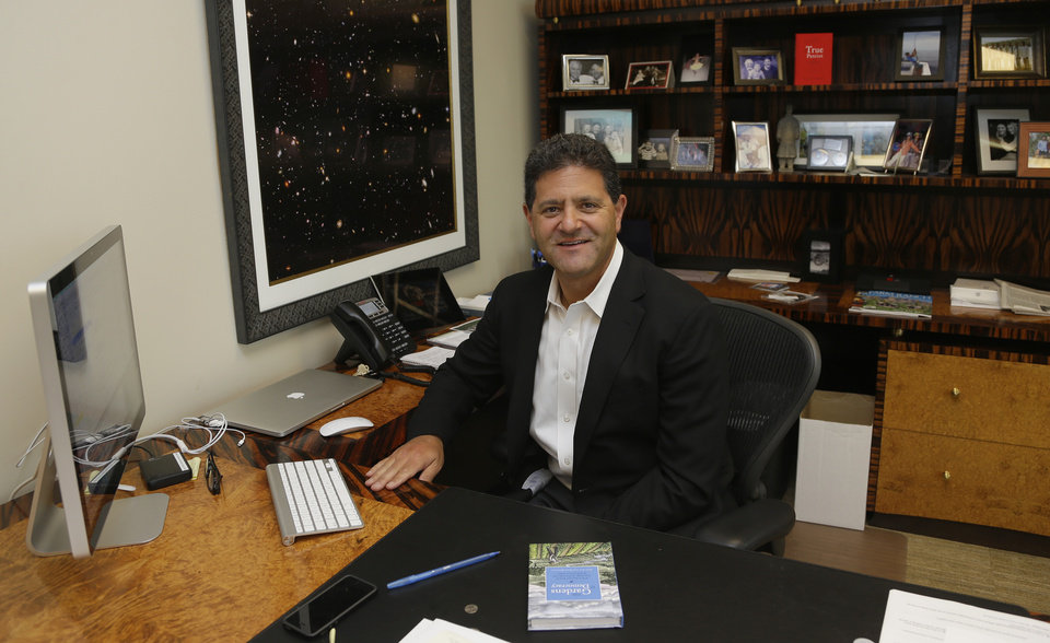 Photo - In this Aug. 2, 2013 photo, Venture capitalist Nick Hanauer poses for a photo in his office in downtown Seattle. Washington state already has the nation's highest state minimum wage at $9.19 an hour, and Hanauer endorses calls to raise it, because he feels putting money in the hands of regular consumers could reduce the drop in demand for goods that he says has hurst our economy.  Hanauer is holding a copy of