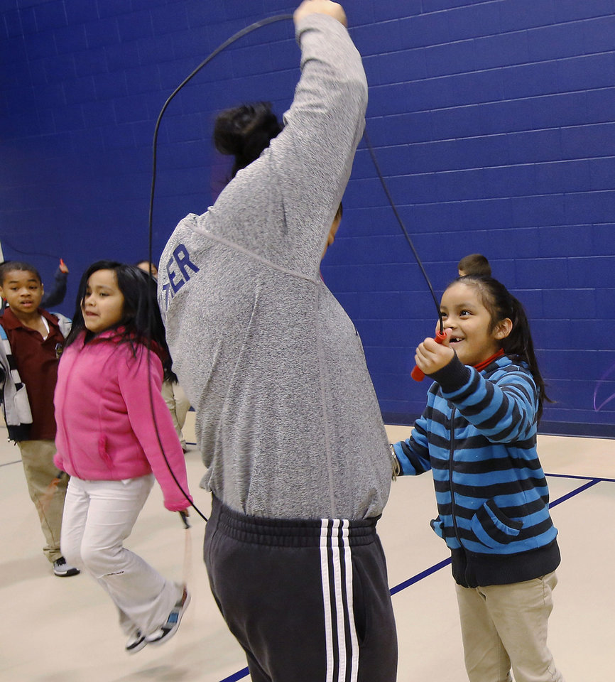 Photo - Second-grader Gladys Morena laughs when her rope gets hung up on the shoulders of  Coach Anita Walker during P.E. class at Coolidge Elementary School in southwest Oklahoma City.  Jim Beckel - THE OKLAHOMAN