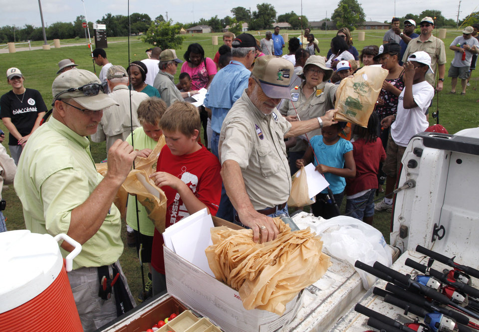 Photo -  Information packets are passed out to children during the Hooked on Fishing event. Photo by Paul Hellstern, The Oklahoman   PAUL HELLSTERN -