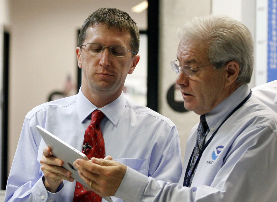 Dr. Rick Knabb, director of the National Hurricane Center, left, talks with Dennis Feltgen, public affairs officer, at the National Hurricane Center in Miami, Tuesday, Aug. 28, 2012. Forecasters at the National Hurricane Center warned that Isaac, especially if it strikes at high tide, could cause storm surges of up to 12 feet (3.6 meters) along the coasts of southeast Louisiana and Mississippi and up to 6 feet (1.8 meters) as far away as the Florida Panhandle. (AP Photo/Alan Diaz) ORG XMIT: FLAD104