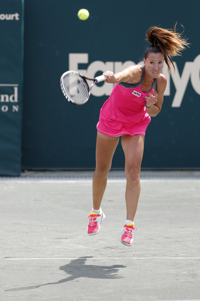 Photo - Jelena Jankovic, of Serbia, serves to Eugenie Bouchard, of Canada, during the Family Circle Cup tennis tournament in Charleston, S.C., Friday, April 4, 2014. (AP Photo/Mic Smith)
