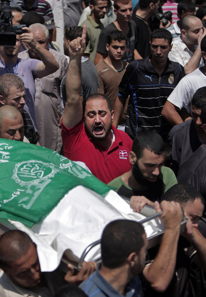 Photo - Mourners chant angry slogans during the funeral of Widad Mustafa Deif, 27, who was killed along with her 8-month-old son Ali Mohammed Deif in Israeli strikes in Gaza City late Tuesday, during their funeral in Jabaliya refugee camp in the northern Gaza Strip, Wednesday, Aug. 20, 2014. Widad was the wife of Mohammed Deif, the leader of the Hamas military wing. (AP Photo/Khalil Hamra)