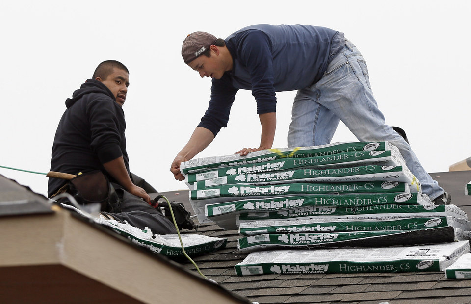Photo - Workers install a roof on a Central Oklahoma Habitat for Humanity home on SE 26 earlier this year. It was the first of many Habitat  houses to be roofed with materials donated by Malarkey Roofing Products.  NATE BILLINGS - THE OKLAHOMAN