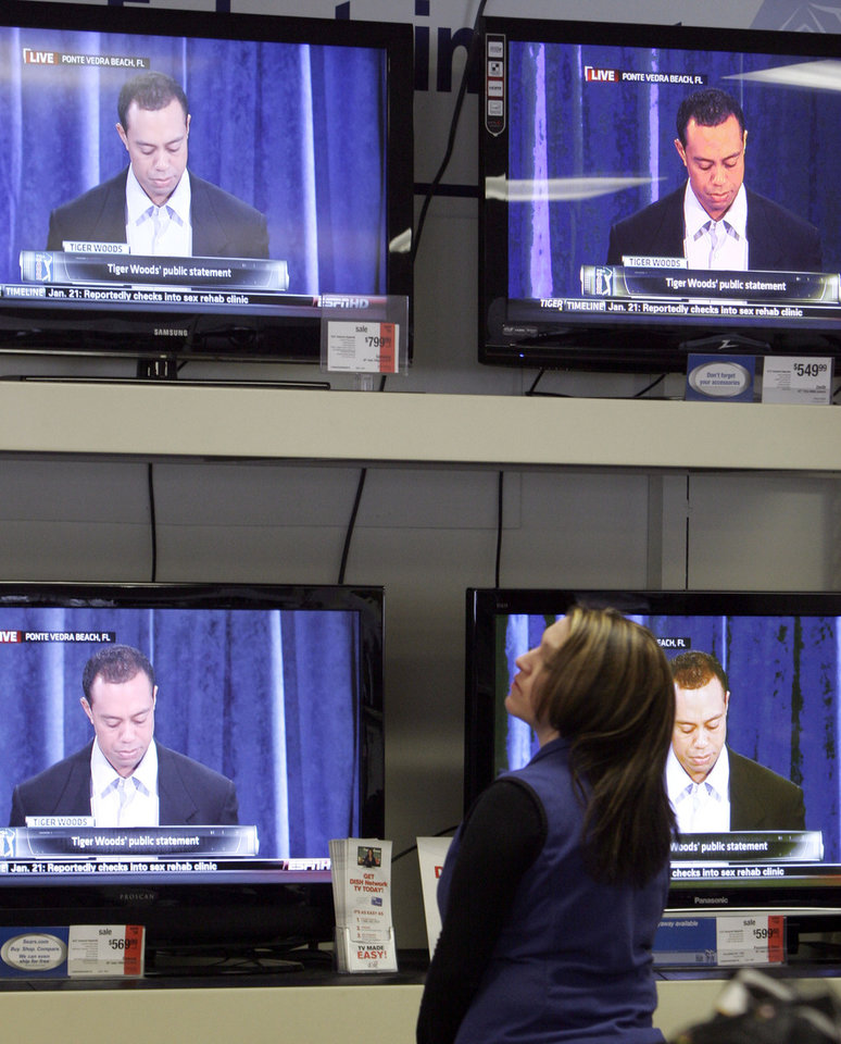 Photo - Employee Caitlyn Lacroix stops to watch Tiger Woods on television at the Sears store in Berlin, Vt., Friday, Feb. 19, 2010. Tiger Woods has apologized for having affairs and says he is unsure when he will return to competitive golf.  Woods talked for more than 13 minutes Friday from the clubhouse at the TPC Sawgrass, home of the PGA Tour. (AP Photo/Toby Talbot) ORG XMIT: MR102
