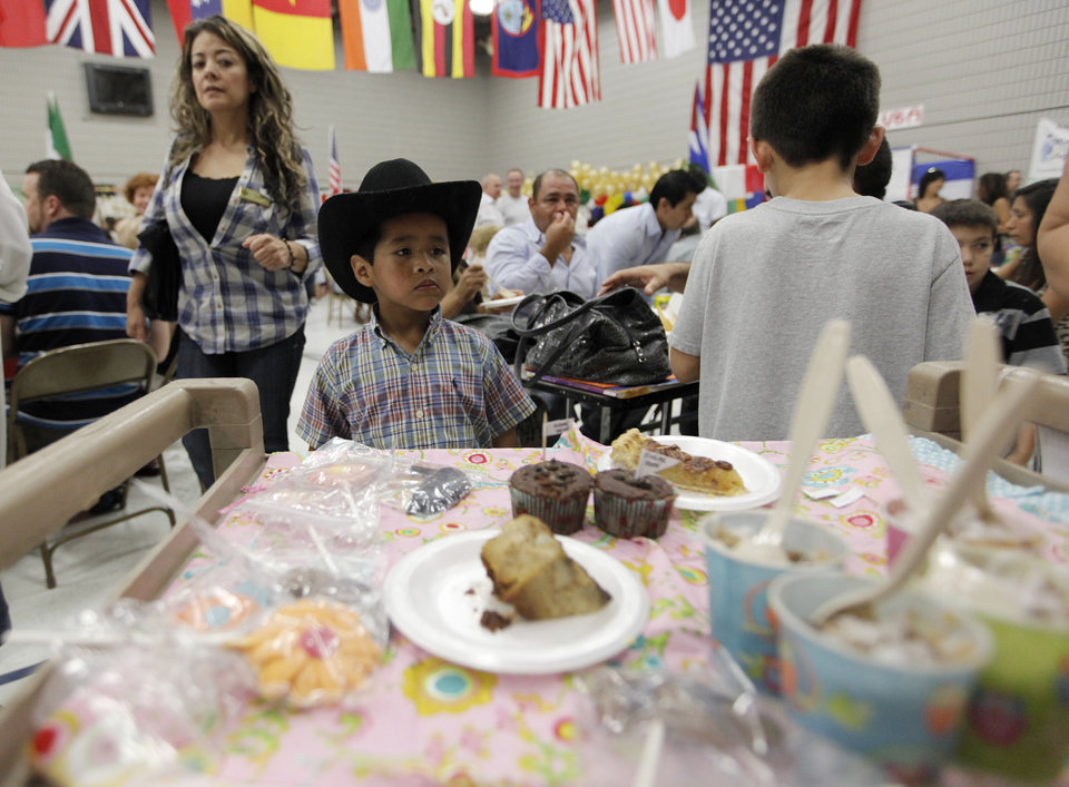Photo - A child looks at a dessert tray during a multicultural food festival at St. Eugene Catholic Church in Oklahoma City, Sunday, Sept. 9, 2012.  Photo by Garett Fisbeck, The Oklahoman  Garett Fisbeck - Garett Fisbeck