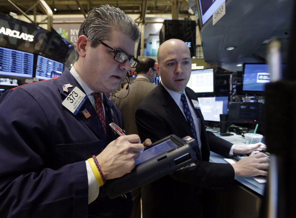 Photo - Trader John Panin, left, and specialist Jay Woods work on the floor of the New York Stock Exchange Tuesday, Jan. 28, 2014. Stocks are higher in early trading on Wall Street as the stock market turns positive after three days of losses. (AP Photo/Richard Drew)
