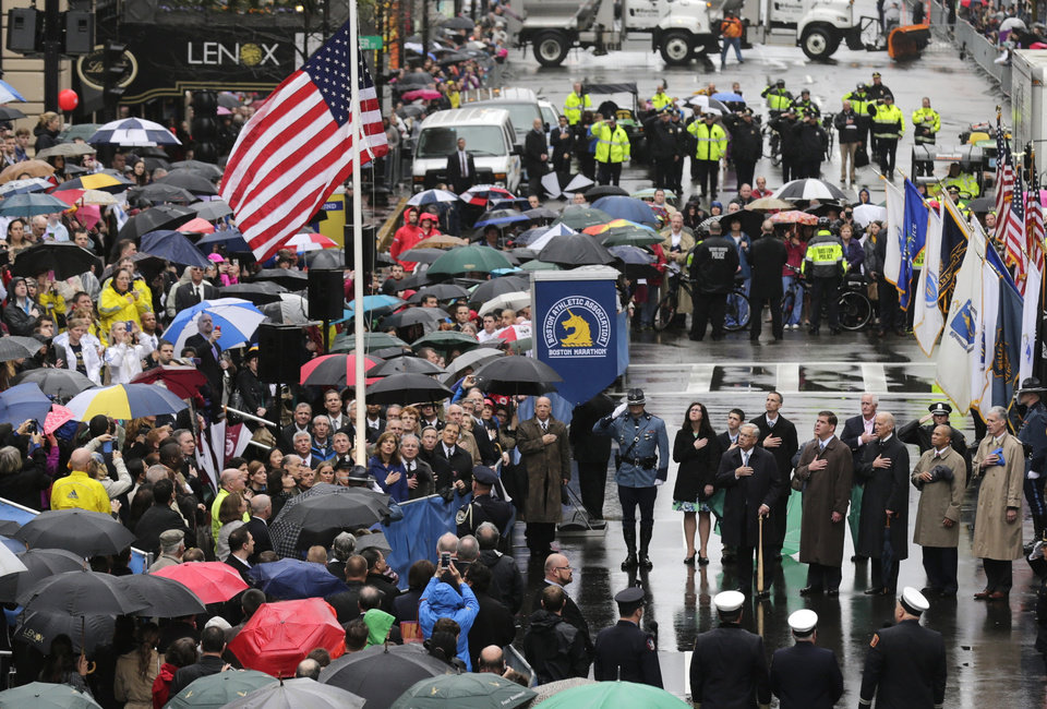 Photo - Survivors, officials, first responders and guests pause as the flag is raised at the finish line during a tribute in honor of the one year anniversary of the Boston Marathon bombings, Tuesday, April 15, 2014 in Boston. (AP Photo/Charles Krupa)