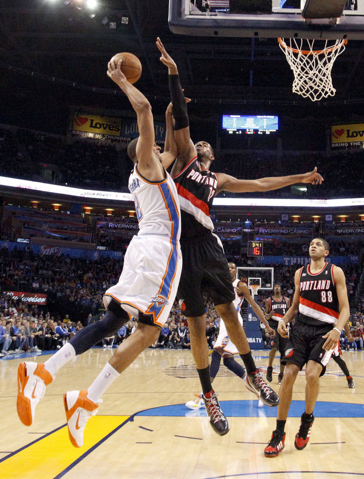 Oklahoma City's Thabo Sefolosha (2) shoots a lay up as Portland's LaMarcus Aldridge (12) defends during the NBA game between the Oklahoma City Thunder and the Portland Trailblazers, Sunday, March 27, 2011, at the Oklahoma City Arena. Photo by Sarah Phipps, The Oklahoman