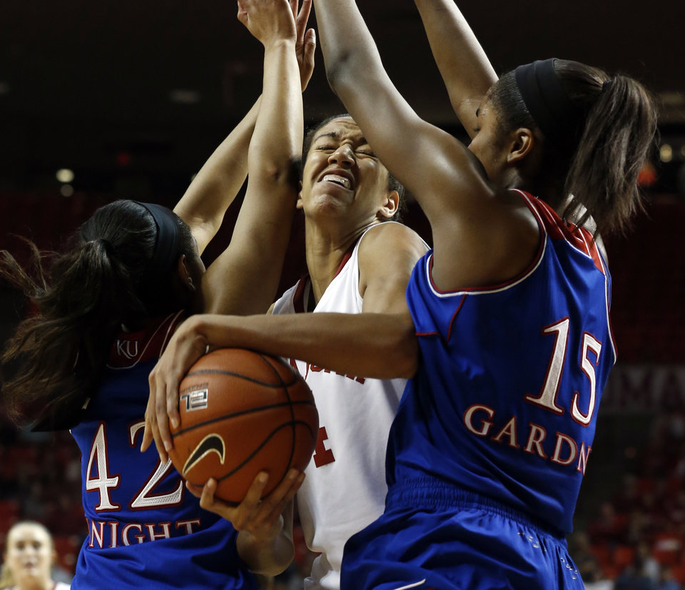 Oklahoma Sooner's Nicole Griffin (4) tries to split Kansas Jayhawk's Natalie Knight (42) and Chelsea Gardner (15) in the lane as the University of Oklahoma Sooners (OU) play the Kansas Jayhawks in NCAA, women's college basketball at The Lloyd Noble Center on Saturday, Feb. 22, 2014  in Norman, Okla. Photo by Steve Sisney, The Oklahoman