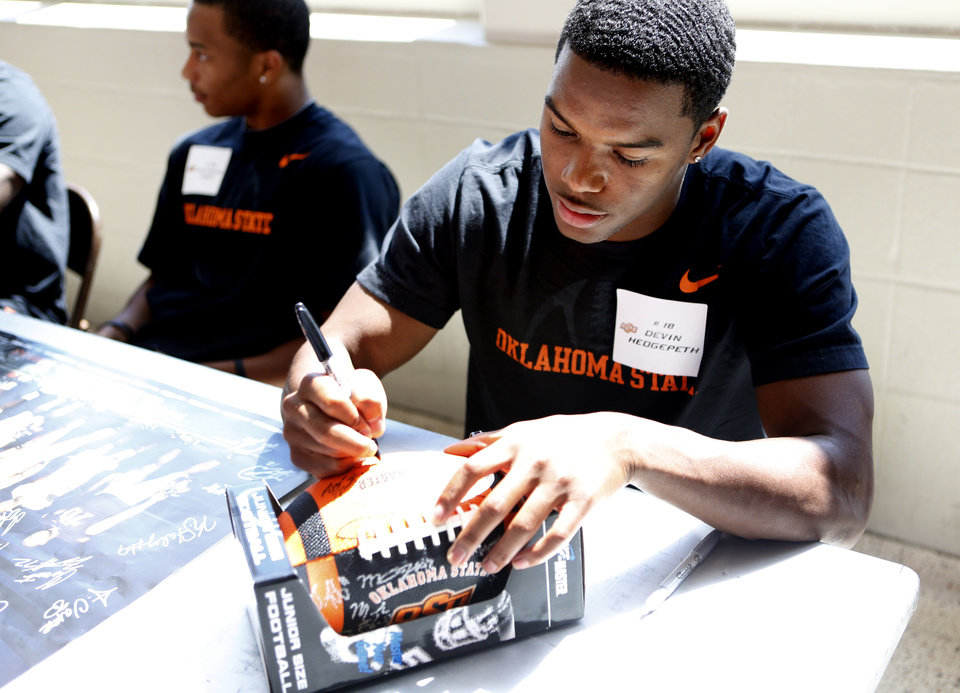 Photo - Devin Hedgepath signs a football during Oklahoma State's Fan Appreciation Day at Gallagher-Iba Arena in Stillwater, Okla., Saturday, Aug. 4, 2012. Photo by Sarah Phipps, The Oklahoman