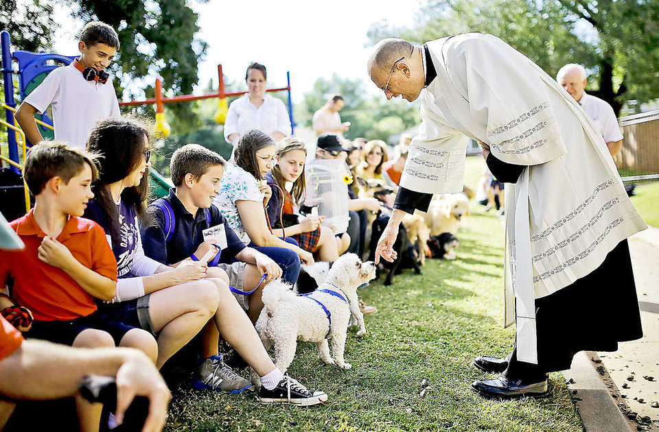 Photo - The Rev. Ray Ackerman visits with a dog during the blessing of the animals on St. Francis of Assisi Feast Day at St. Elizabeth Ann Seton Catholic School.    Photo by Chris Landsberger, The Oklahoman  CHRIS LANDSBERGER - CHRIS LANDSBERGER
