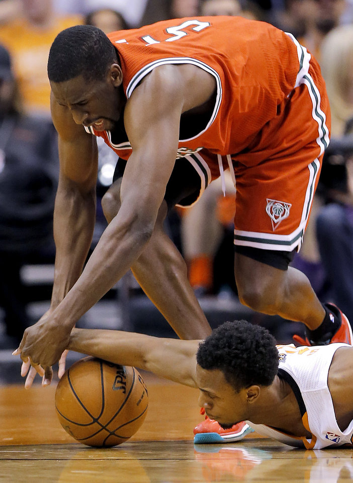 Phoenix Suns' Ish Smith, on floor, battles Milwaukee Bucks' Ekpe Udoh for the ball during the first half of an NBA basketball game, Saturday, Jan. 4, 2014, in Phoenix. (AP Photo/Matt York)