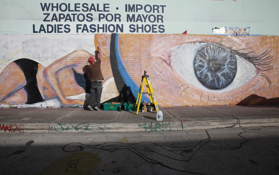 Photo - Artist Scott Debus spray-paints a mural on the wall of a warehouse in the Wynwood district of Miami, Monday, Dec. 3, 2012. Art Basel Miami Beach and about two dozen other independent art fairs open Thursday. Tens of thousands of people are expected through Sunday at the fairs throughout Miami and South Beach. (AP Photo/Wilfredo Lee)