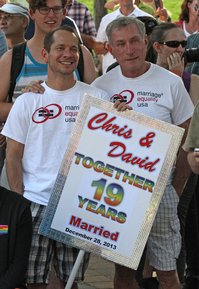 Photo - David Tuma, left, and his spouse Chris Johnson gather with about 300 people gathered in a downtown park to celebrate the gay marriage ruling Wednesday, June 25, 2014, in Salt Lake City. Tuma and Johnson were married Dec. 28th, 2013. A federal appeals court on Wednesday ruled for the first time that states must allow gay couples to marry, finding the Constitution protects same-sex relationships and putting a remarkable legal winning streak across the country one step closer to the U.S. Supreme Court. (AP Photo/Rick Bowmer)