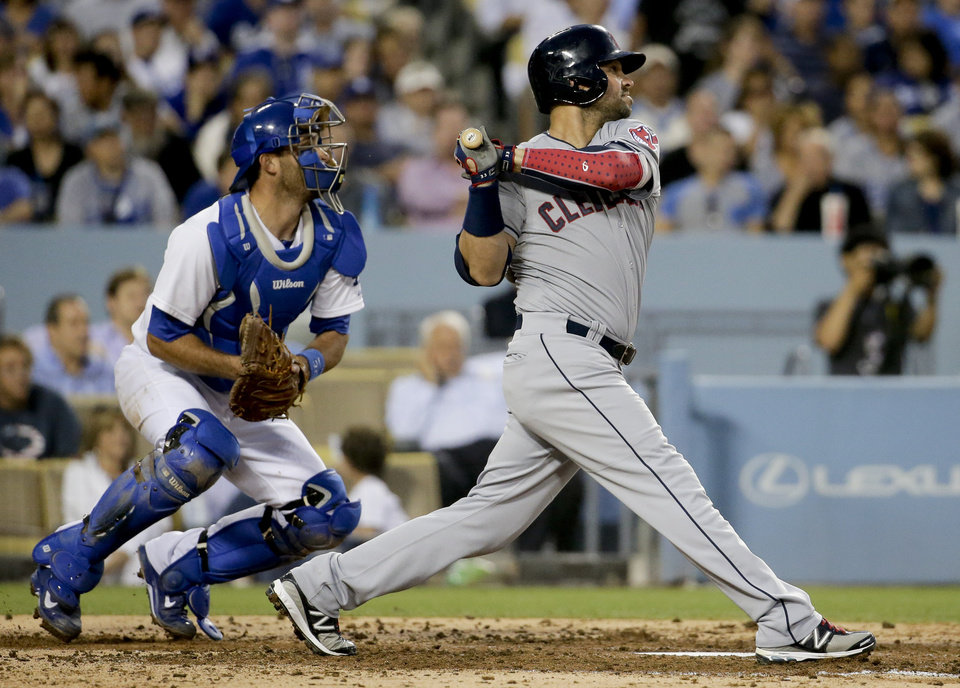 Photo - Cleveland Indians' Nick Swisher, right, watches his two-RBI double as Los Angeles Dodgers catcher Drew Butera looks on during the third inning of a baseball game in Los Angeles, Tuesday, July 1, 2014. (AP Photo/Chris Carlson)
