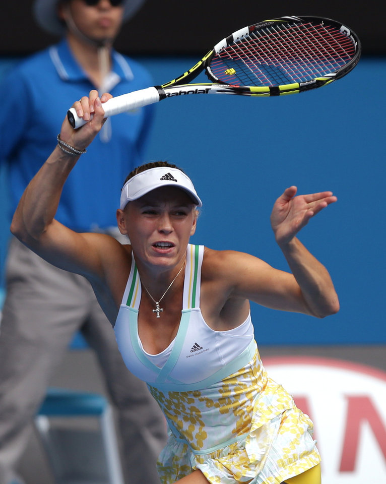 Photo - Caroline Wozniacki of Denmark hits a shot  to Garbine Muguruza of Spain during their third round match at the Australian Open tennis championship in Melbourne, Australia, Saturday, Jan. 18, 2014.(AP Photo/Aaron Favila)