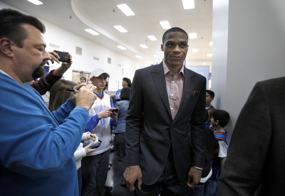 Photo - Fans take pictures of Oklahoma City's Russell Westbrook as he leaves a press conference at the Thunder Community Events Center in Oklahoma City, Sunday, Jan. 22, 2012. Photo by Sarah Phipps, The Oklahoman