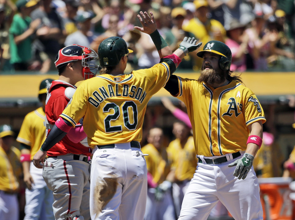 Photo - Oakland Athletics' Derek Norris, right, celebrates his three-run home run with teammate Josh Donaldson (20) during the first inning of a baseball game against the Washington Nationals, Sunday, May 11, 2014, in Oakland, Calif. (AP Photo/Marcio Jose Sanchez)