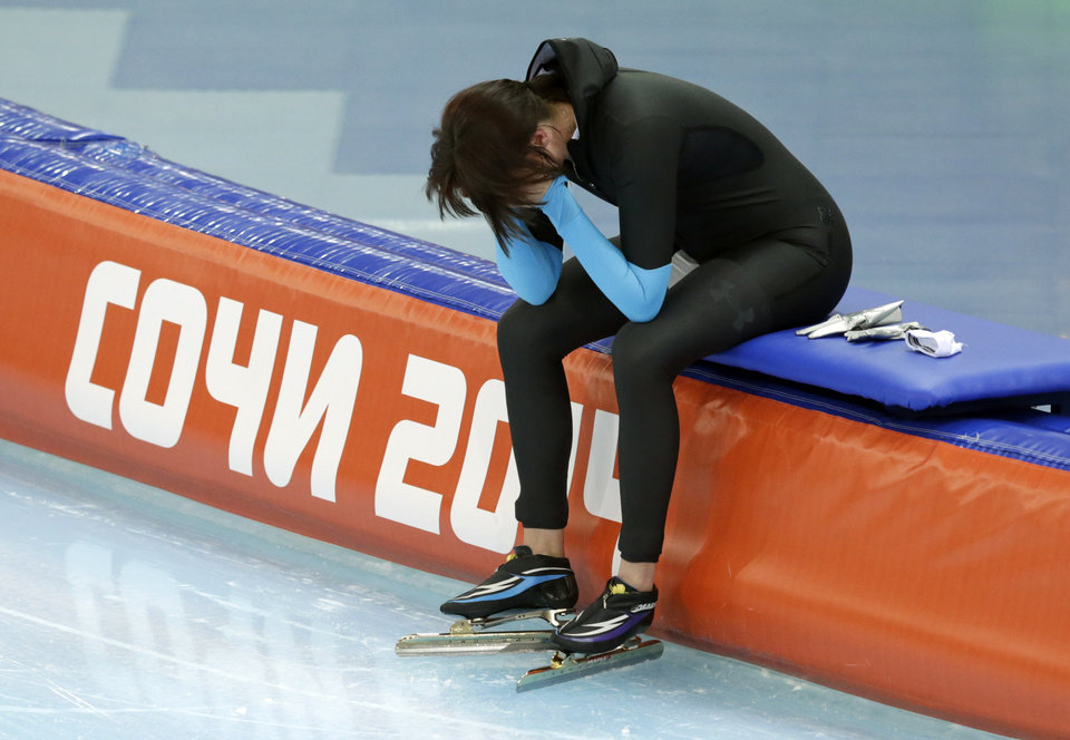 Photo - Heather Richardson of the U.S. cups her face and looks down after competing in the women's 1,500-meter race at the Adler Arena Skating Center during the 2014 Winter Olympics in Sochi, Russia, Sunday, Feb. 16, 2014. (AP Photo/Matt Dunham)