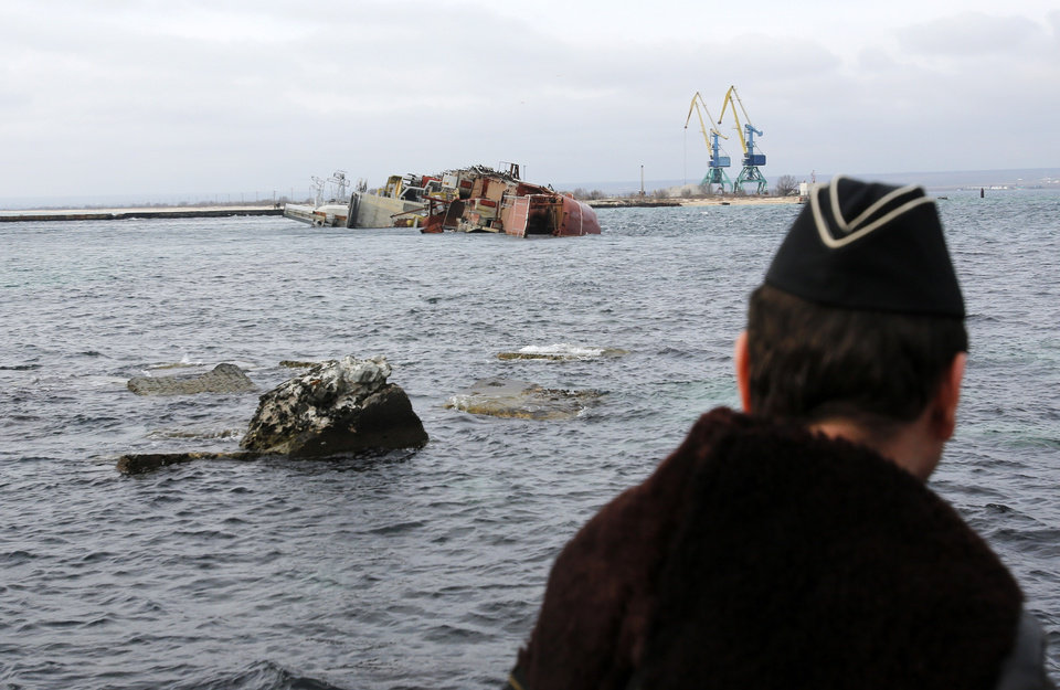 Photo - A Ukrainian Navy officer looks at the scuttled decommissioned Russian vessel