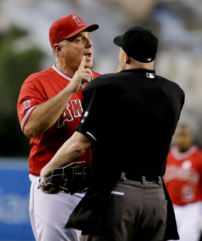 Photo - Los Angeles Angels manager Mike Scioscia argues a call with Mike Estabrook, right, during the first inning of a baseball game against the Philadelphia Phillies in Anaheim, Calif., Tuesday, Aug. 12, 2014. (AP Photo/Chris Carlson)