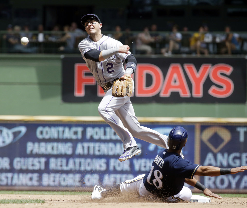 Photo - Milwaukee Brewers' Khris Davis is out at second as Colorado Rockies' Troy Tulowitzki turns a double play on a ball hit by Mark Reynolds during the second inning of a baseball game Sunday, June 29, 2014, in Milwaukee. (AP Photo/Morry Gash)