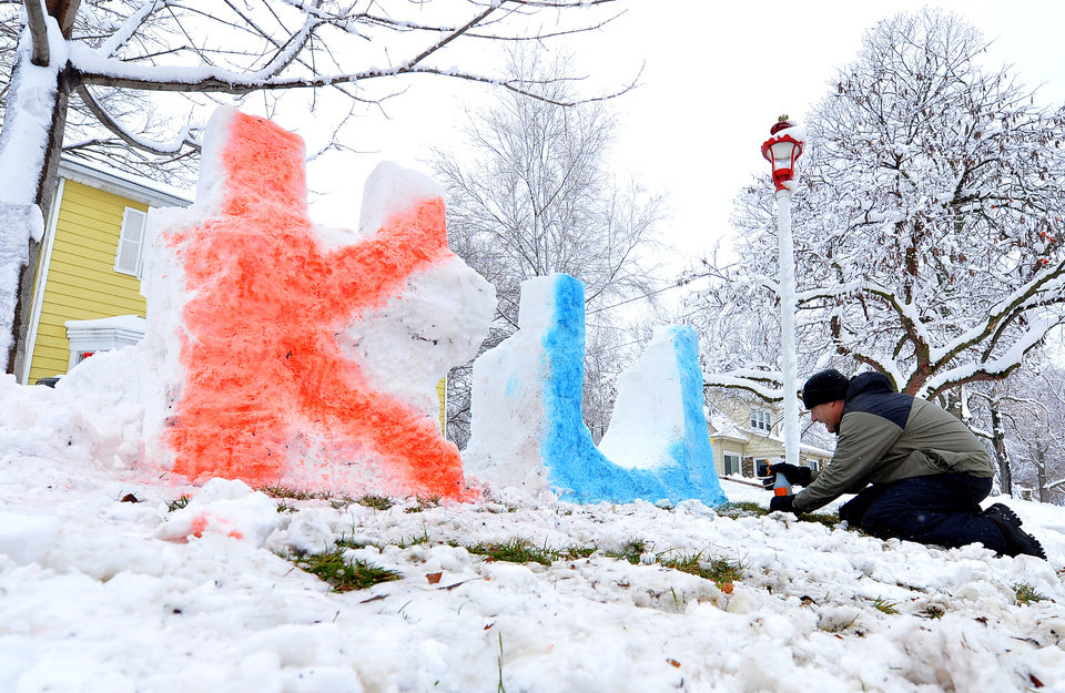 Photo - University of Kansas alum Geoff Folker applies food coloring to his snow sculpture at his home on Park Street in Olathe, Kan., on Sunday, March 24, 2013.  A storm that dumped up to 15 inches of snow on parts of Colorado and Kansas is making its way east, with winter storm warnings and advisories issued for today and tomorrow as far east as Pennsylvania. (AP Photo/The Kansas City Star, John Sleezer)