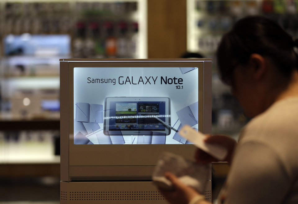 A woman walks by a billboard of Samsung Electronics\'s Galaxy Note 10.1 at a showroom of its headquarters in Seoul, South Korea, Friday, Oct. 5, 2012. Samsung Electronics Co. tipped all-time high quarterly operating profit, likely driven by strong sales of high-end smartphones that offset weak semiconductor orders. (AP Photo/Lee Jin-man)
