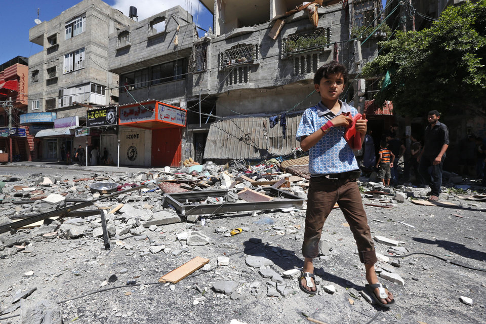 Photo - A Palestinian boy walks on debris of a destroyed building hit by an Israeli strike in Gaza City, northern Gaza Strip, Friday, July 18, 2014. Israeli troops pushed deeper into Gaza on Friday to destroy rocket launching sites and tunnels, firing volleys of tank shells and clashing with Palestinian fighters in a high-stakes ground offensive meant to weaken the enclave's Hamas rulers. (AP Photo/Lefteris Pitarakis)