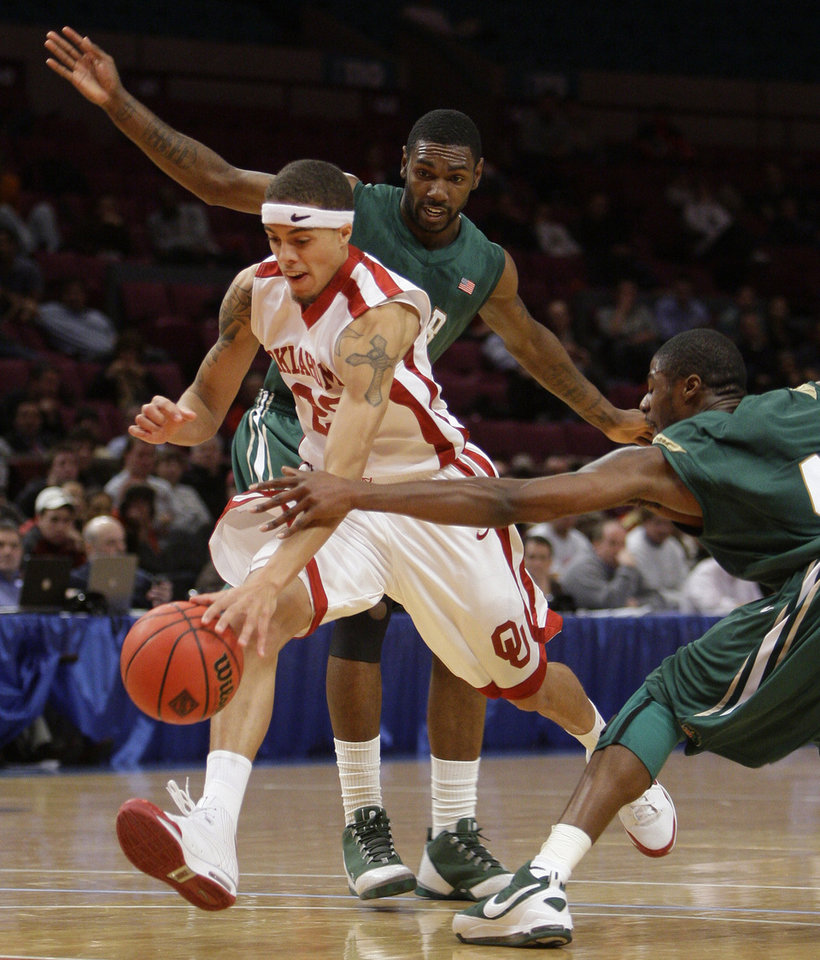 Photo - NIT SEASON TIP-OFF / OU / UNIVERSITY OF ALABAMA AT BIRMINGHAM: University of Oklahoma guard Austin Johnson, center, splits the defense of UAB's Lawrence Kinnard, left, and Paul Delaney in the first half during a semifinal of the preseason NIT college basketball tournament Wednesday, Nov. 26, 2008, at Madison Square Garden in New York. (AP Photo/Julie Jacobson) ORG XMIT: NYJJ110