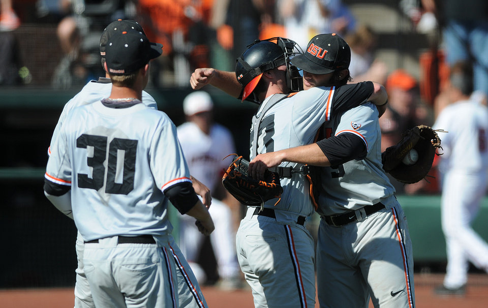 Photo - Oregon State catcher Logan Ice (33) hugs pitcher Ben Wetzler while teammage Michael Howard (30) joins in the Beavers celebration of defeating UNLV 6-1 in an NCAA college baseball regional tournament game in Corvallis, Ore., Sunday, June 1, 2014. (AP Photo/Mark Ylen)
