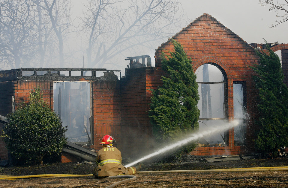 Photo - FIRE / HOUSE: A Nicoma Park firefighter sprays water on a house in the Oakwood East housing addition as wildfires burned multiple homes in Midwest City  Thursday, April 9, 2009.  Photo by JIM BECKEL, THE OKLAHOMAN ORG XMIT: KOD