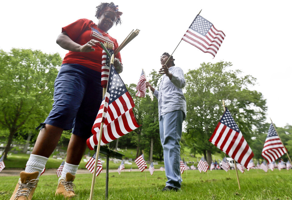 Photo - Rachelle Coburn, left, and Quiana Reeves participate with other staff and day program participants from Pittsburgh Mercy Intellectual Disabilities Services and volunteer to place flags on the graves of veterans at the Allegheny Cemetery in Pittsburgh, Wednesday, May 23, 2018, for the upcoming Memorial Day holiday weekend. (AP Photo/Keith Srakocic)