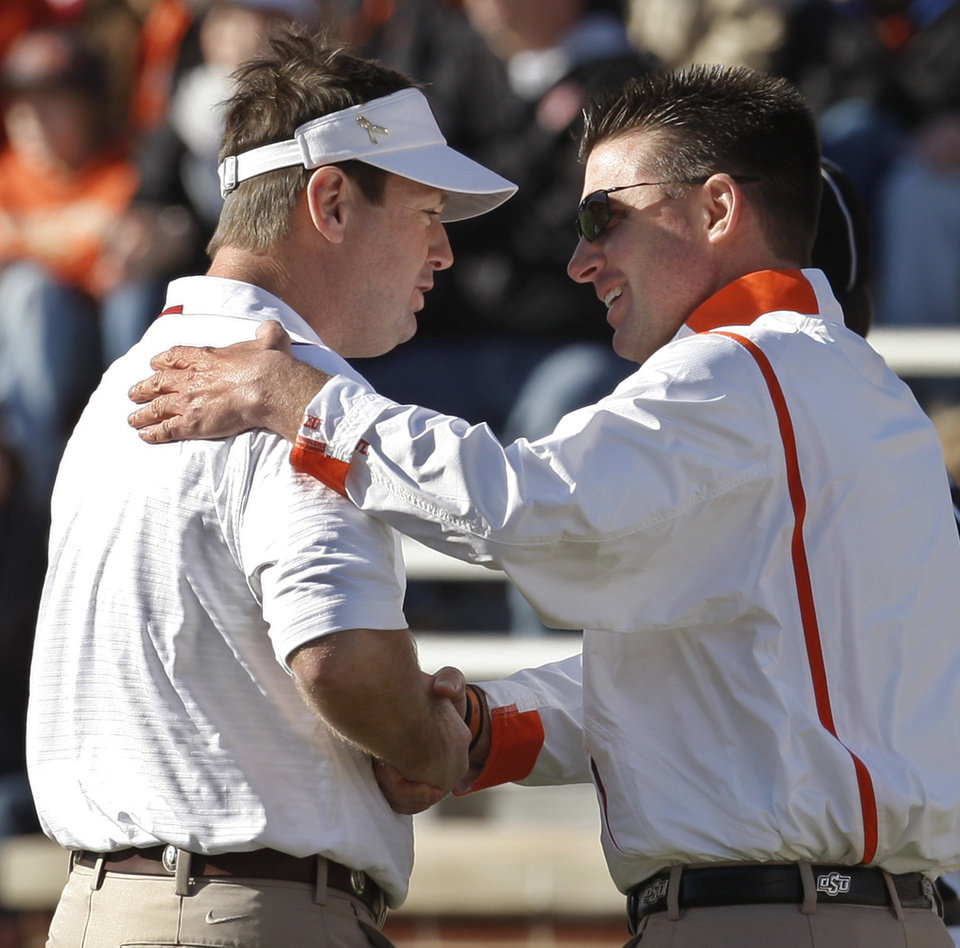 Photo - Oklahoma head coach Bob Stoops, left, and Oklahoma State head coach Mike Gundy, right, shake hands before the start of an NCAA college football game in Norman, Okla., Saturday, Nov. 28, 2009. AP Photo