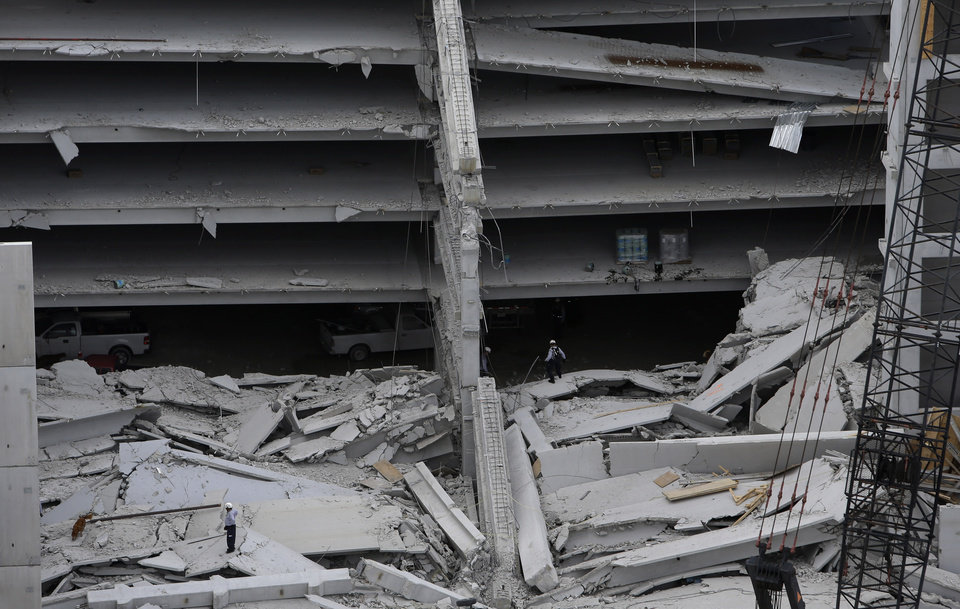 A dog walks through the rubble, lower left, with rescue workers at a five-story parking garage after it collapsed at Miami-Dade College, Wednesday, Oct. 10, 2012 in Miami, killing one worker and trapping two others in the rubble, officials said. Several other workers were hurt, including one rescued from the debris. (AP Photo/Lynne Sladky)