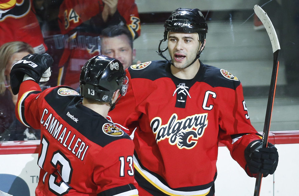 Photo - Calgary Flames' Mark Giordano, right, celebrates his goal with teammate Mike Cammalleri during the first period of an NHL hockey game against the New York Rangers in Calgary, Alberta, Friday, March 28, 2014. (AP Photo/The Canadian Press, Jeff McIntosh)