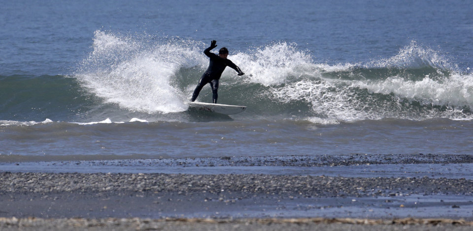 Photo - In this June 3, 2014 photo, a surfer catches a wave at the mouth of the Elwha River near Port Angeles, Wash. The final chunks of concrete are expected to fall this September in the nation's largest dam removal project, but nature is already reclaiming the Elwha River on Washington's Olympic Peninsula. (AP Photo/Elaine Thompson)