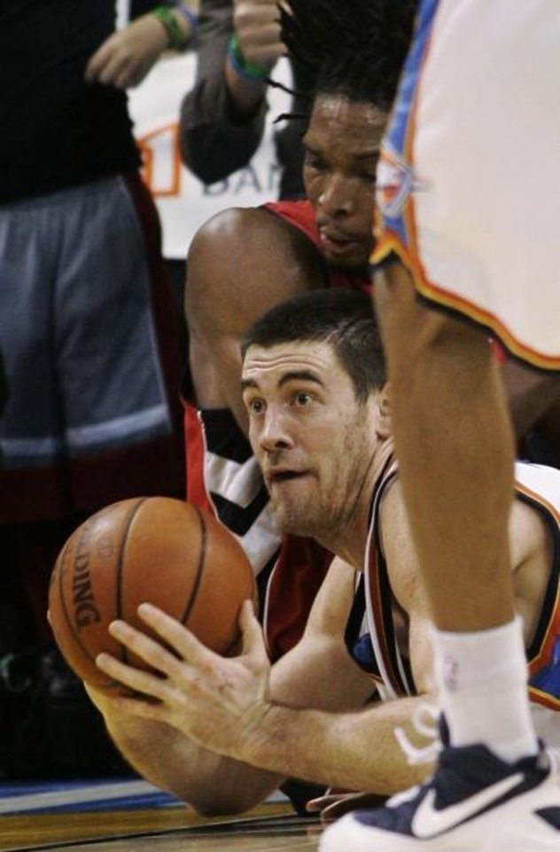 Photo -  The Thunder is retiring Nick Collison's number Wednesday night even though he spent much of his 14-year career as a role player. That didn't keep him from regularly going to the floor after a loose ball as he did during the 2008-09 season against Toronto's Chris Bosh. [AP PHOTO]