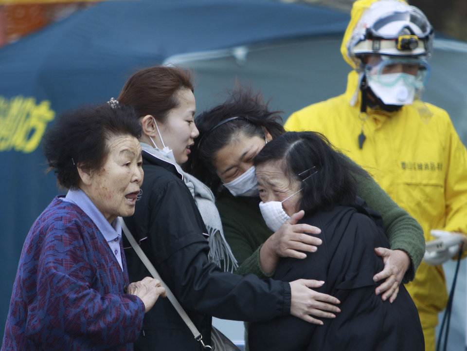 Photo - FILE - In this March 13, 2011 file photo, residents evacuated from areas surrounding the Fukushima nuclear facilities damaged by the March 11 massive earthquake and tsunami react during a check for radiation contamination in Koriyama city, Fukushima prefecture, Japan. Influential Japanese scientists who help set national radiation exposure limits have for years had trips paid for by the country's nuclear plant operators to attend overseas meetings of the world's top academic group on radiation safety. Some of these same scientists have consistently given optimistic assessments about the health risks of radiation, interviews with the scientists and government documents show. Their pivotal role in setting policy after the March 2011 tsunami and ensuing nuclear meltdowns meant the difference between schoolchildren playing outside or indoors and families staying or evacuating.  (AP Photo/Wally Santana, File)