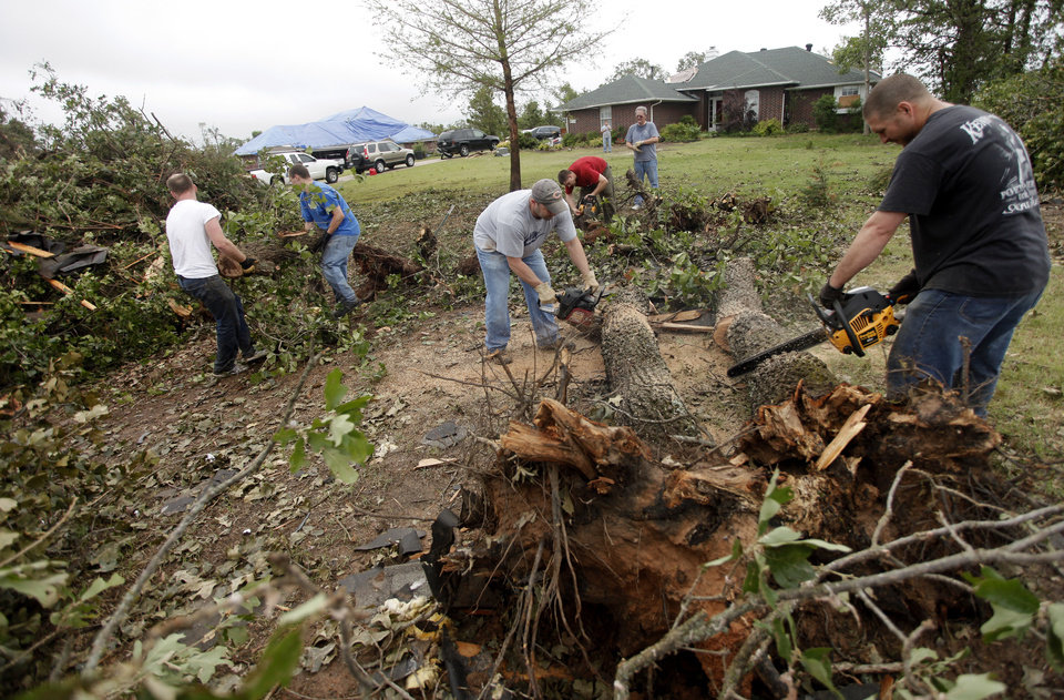 People clear fallen trees in the Dripping Springs Estates Saturday, May 15, 2010. Saturday hundreds of volunteers went into areas that had been affected by last week's tornadoes to help clear debris. Photo by Doug Hoke, The Oklahoman.
