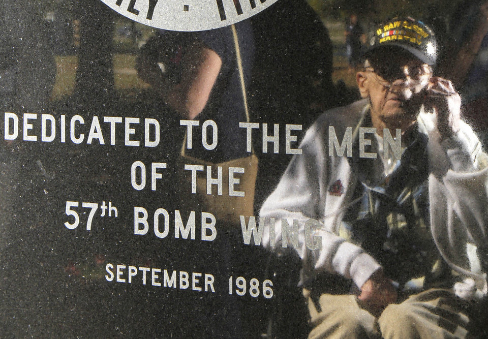 Photo - In this Sept. 27, 2013 photo Lenard Wichtowski is reflected in the memorial to the 57th Bomb Wing during a reunion outside the U.S. Air Force Museum at Wright Patterson Air Force base in Dayton, Ohio. According to the Department of Veteran Affairs, just a little over 1 million World War II veterans remain. They are in their 80s and 90s, and many are infirm or fragile. The sparsely attended reunions are yearly reminders of the passing of the Greatest Generation. (AP Photo/Tom Uhlman)